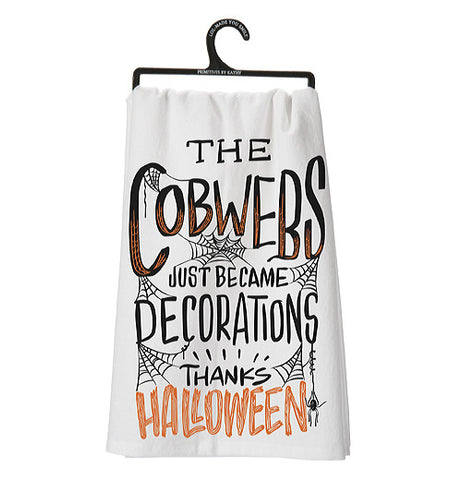 "White dish towel that says ""The Cobwebs Just Became Decorations Thanks Halloween"" in black and orange lettering with white as the background hanging from a black hanger."