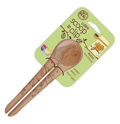 "This beechwood spoon has a set of two handles very close together. On the two handles are pictures of flowers on tree branches. At the top of the spoon, holding a flower, is a hedgehog. The spoon is attached to its green packaging with the words, ""Coffee Scoop & Clip"" in brown lettering."