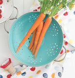 Metal Turquoise Colander with Handles and a Display of Carrots