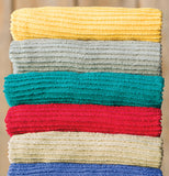 The teal towel is shown in the middle of a stack of towels.