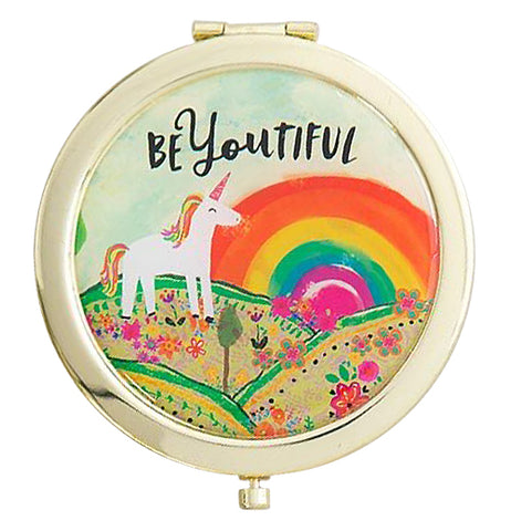 "The close-up of the Compact Mirror features a unicorn stand in front of a rainbow with text that says ""BeYoutiful""."