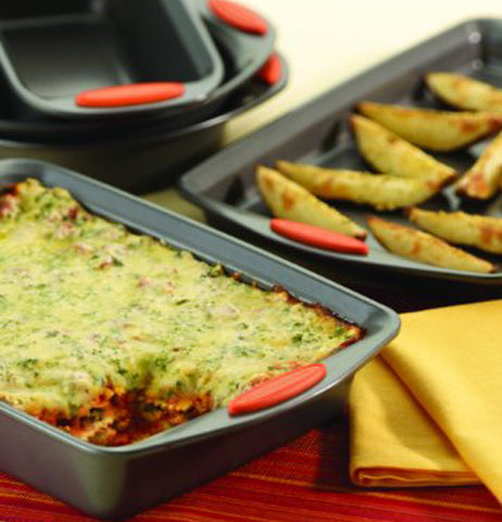 Lasagna and potato wedges are shown being served from two pans.