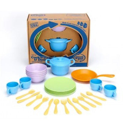 This child's play set includes four blue cups, four green plates, an orange skillet, a blue pot with lid, four purple bowls, and four sets of yellow knives, forks, and spoons, displayed in front of the packaging