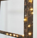 The lights are shown wrapped around a wooden frame.