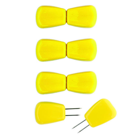 6 set of corn holders shaped like corn kernals they are yellow with metal tips