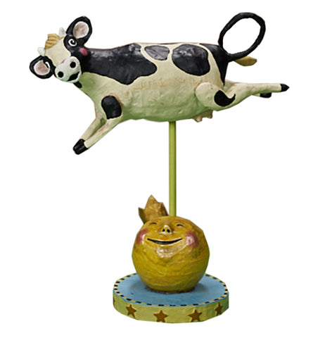 This figurine is of a smiling black and white cow in midair over a smiling yellow moon sitting on a blue and yellow stand with red stars around it.