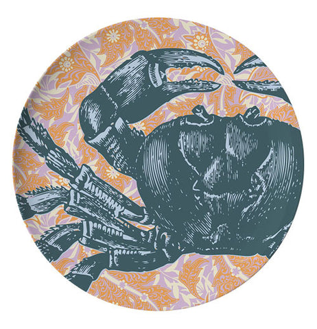 This plate has a design of a dark blue crab against an orange oceanic background.