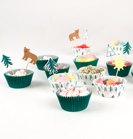 "Eleven of the ""Let's Explore"" cupcakes six are green and five are white with green pine trees filled with candy and decorated with bears, trees, sun, and teepees toppers."