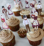 Pilgrim toppers playing musical instruments are on cupcakes.