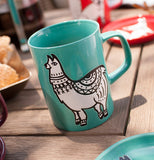 The turquoise ceramic mug with a llama is shown next to a coaster with the same design sitting on a wooden table.