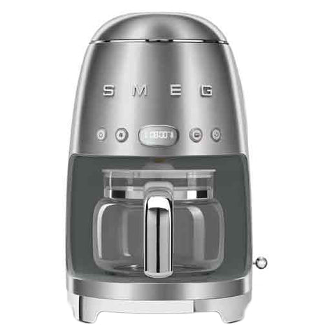 "A stainless steel coffee machine with a coffee carafe set up inside it. The base has small ""feet"" that elevate it slightly. The brand name ""Smeg"" and buttons are across the body."