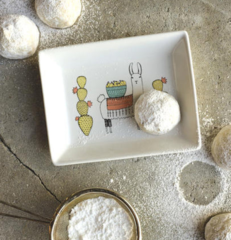 "The powdered sugar cookie sits on a ""Llamarama"" Glass Tray on a wooden countertop."