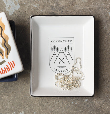 "The ""Adventure Awaits"" Glass Tray sits on a marble table."
