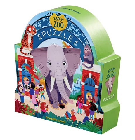 """Day at the Zoo"" 48 piece puzzle in its blue and green rounded box with design of people visiting the zoo, a giant arch along the top and a giant elephant taking up the middle of the picture.."