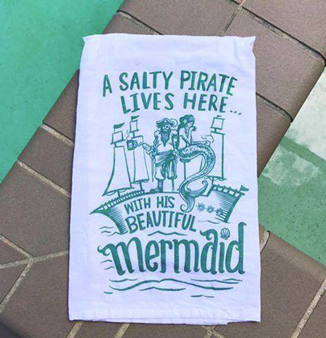 White and teal dish towel with a pirate, a mermaid, and a ship.