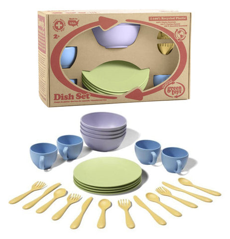 This child's play set includes four green plates, four blue cups, four purple bowls and fours sets of knives, spoons and forks displayed in front of the set in its original packaging.
