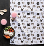 Cat's meow dish towel laying out like a picnic blanket with veggies, drinks and silverware on it.