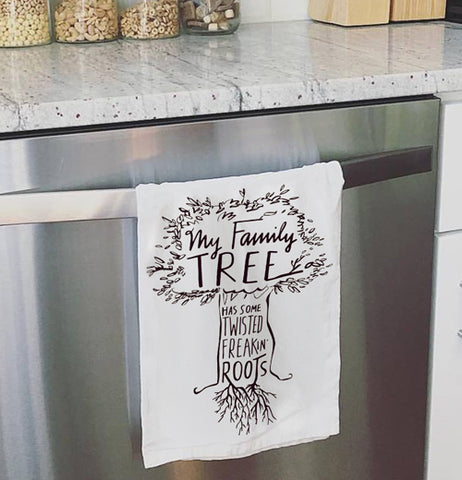 Family tree dish towel hanging on the oven door.