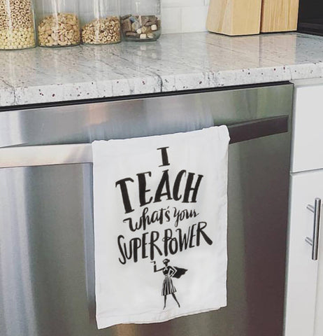 "White dish towel hanging on a dishwasher, with a super hero woman at the bottom, that says ""I teach what's your superpower."""