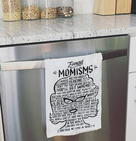 "White dish towel that contain word ""Momisms"" and other words relating to a mother shaped like a woman in black text hanging over a dishwasher."