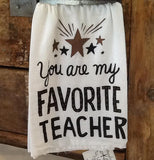 "The white towel with the different colored stars and the words, ""You are my Favorite Teacher"" in white lettering is shown hanging from a drawer."