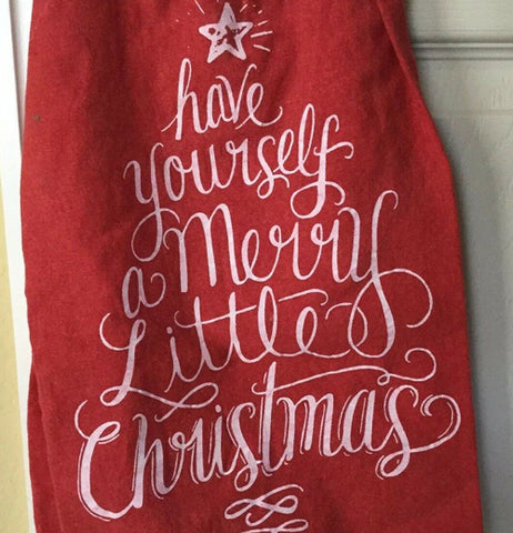 "The red dish towel with the words, ""Have Yourself A Merry Little Christmas"" in white lettering is shown hanging from an oven door."