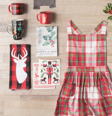 This red and black tea towel with the deer display with holiday mugs and a plaid apron.