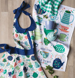 This is a apron that has tea kettles and cups along side a dish towel with the tea kettles and cups on it and on that is light green and white plaid design and a blue cup and sugar bowl sitting on top of the towels