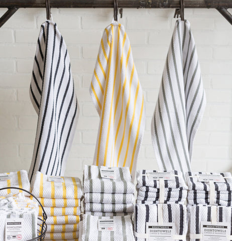 Three basket weave dish towels, one white with black stripes, one white with grey stripes, and one yellow with yellow stripes, are hanging on hooks while their counterparts in their packaging are set out below them in piles.