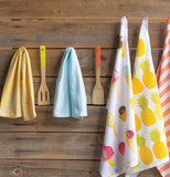 several sets of towels hanging on a wall along with some spatulas two are one straight yellow and one straight blue and one straight ice cream towel and one pineapple towel and one orange striped towel.