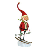 This Santa Claus figurine is shown skiing on a silver white snow base on brown skis with silver poles.