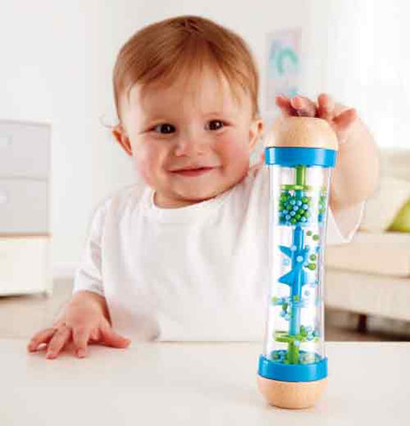 A caucasian toddler plays with a wooden and plastic toy that has a transparent middle. The middle has plastic beads going down a spiral.
