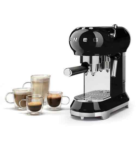 A black expresso machine with 4 glass cups next to it filled with coffee.