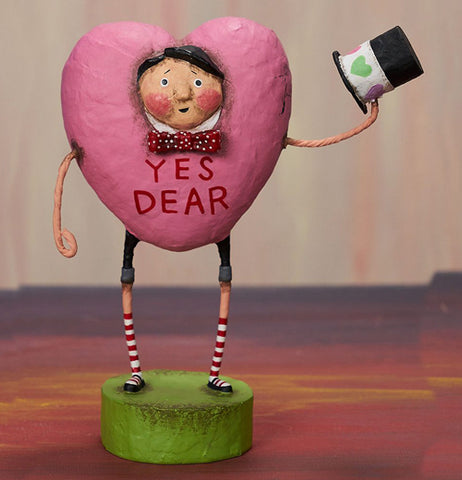 Resin man figurine placed on a table dressed in a pink heart costume holding a black top hat with a green heart decorated sash.