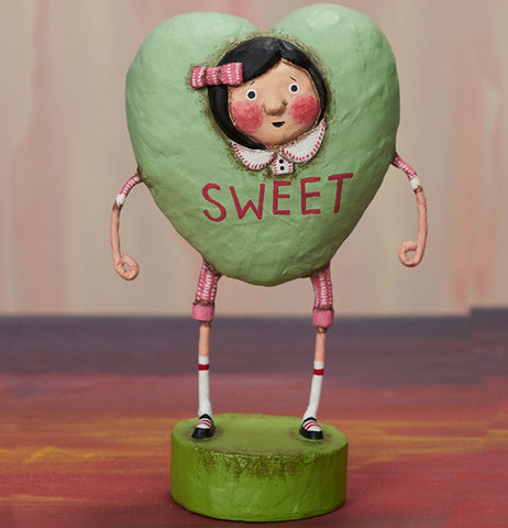 Female resin figurine placed on a table standing on a green stand wearing a green heart costume that says sweet with a pink ribbon in her hair.