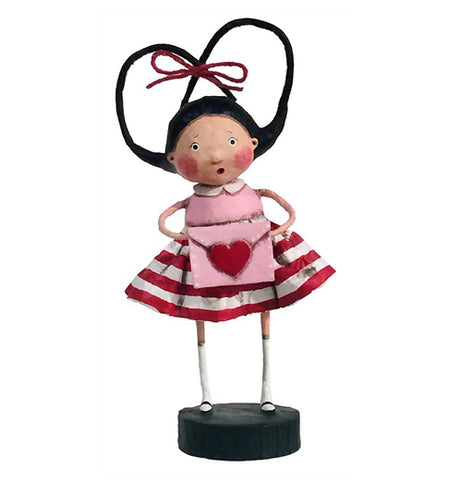 Girl figurine with pig tails tied with a red ribbon in a heart shape wearing a pink blouse and red and white striped skirt holding a pink envelope with red heart on it.