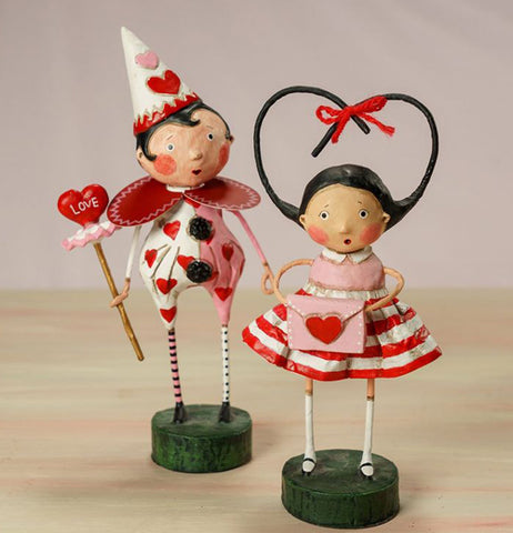 Boy and girl Valentines Day figurines. Boy in a clown costume holding a wand with heart on the end. Girl in a pink blouse and red and white striped skirt combo holding a pink envelope with a heart.