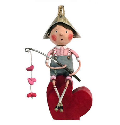 Fishing boy is holding a fishing pole with three hearts on it and sitting on a heart. He has a paper hat on with a pink shirt blue shorts.
