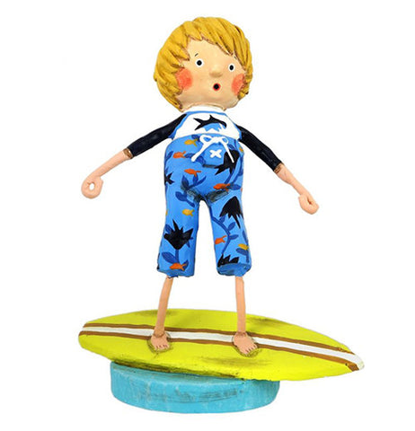 This figurine is of a boy standing on a yellow surf board, dressed in a blue outfit with fish on it.