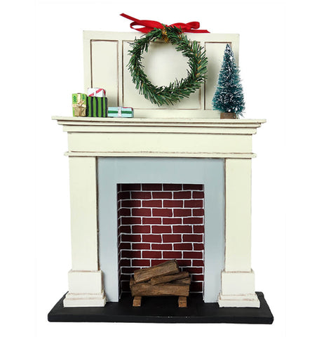 This miniature sculpture is of a fireplace with logs in it and a Christmas wreath hanging above the mantle. On the mantle sits a miniature Christmas tree and some wrapped presents.
