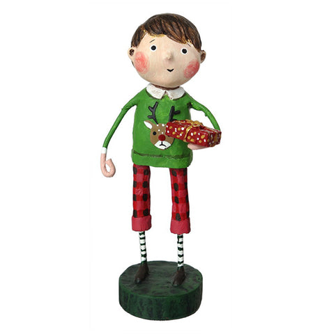 This figurine is of a boy dressed in red pants with black spots, and a green sweater with a reindeer's head. The boy holds a present wrapped in red paper in his right hand.
