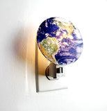 The nightlight shaped to look the earth is shown in use.