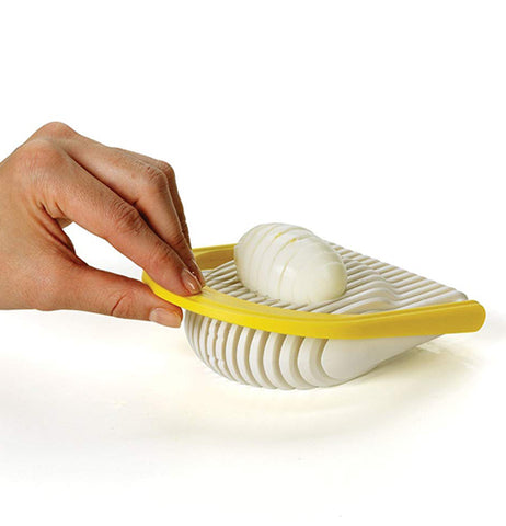 A hand is using a yellow Flipside egg slicer to slice an egg.