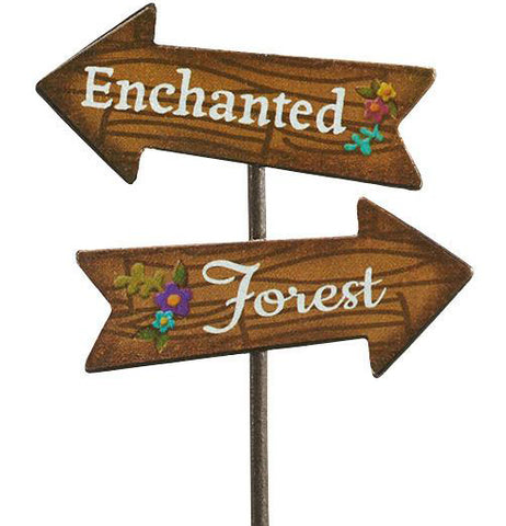 "Zoomed in view of double wooden arrow sign, one says ""Enchanted"" pointing to the left the other says "" Forest pointing to the right. Both have a purple and blue flower on them."