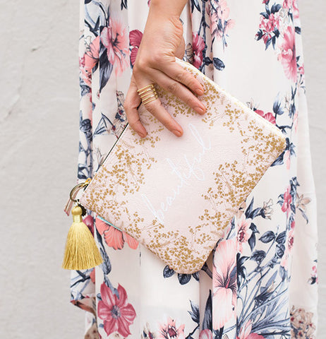 A lady walking and holding her beautiful pocket clutch.