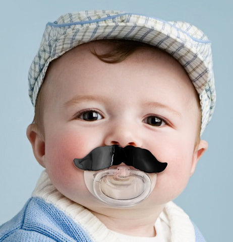 "A sweet baby sucking on a Chill Baby ""Mustache"" Pacifier."