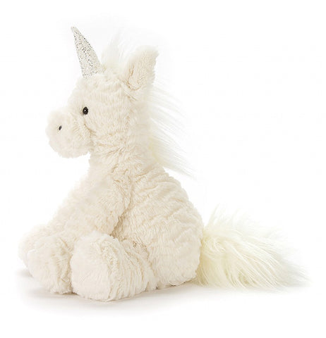 The white stuffed unicorn toy is shown from a side profile angle.