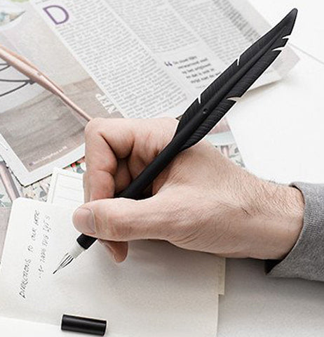 A man's hand is shown writing a note with a black pen shaped like a feather.