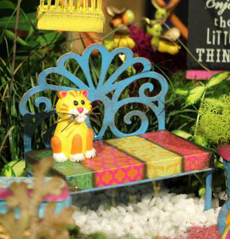 A small cat sculpture is shown sitting on the multi-colored bench within a small garden setting.