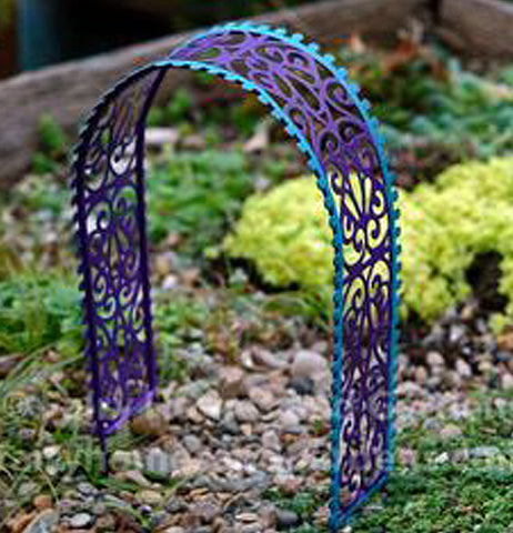 A gypsy style arbor arch with purple and blue filigree heart pattern surrounded by green plants and rocks.